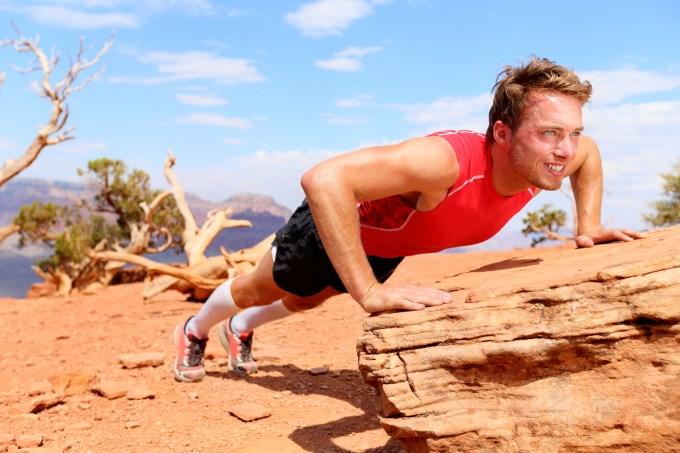 岩を台にインクラインプッシュアップをする男性