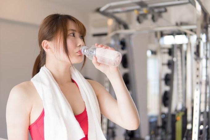飲み物を飲むジムで身体を鍛える日本人女性