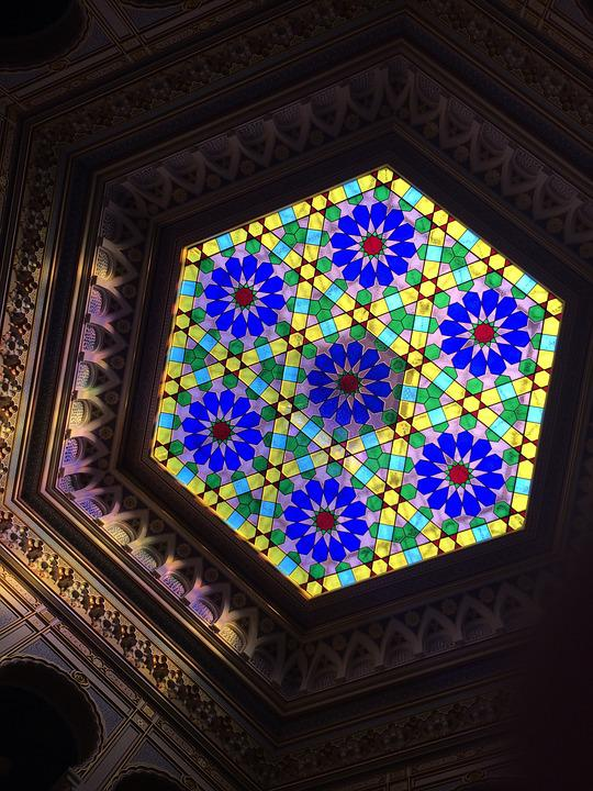 A stained glass window with 7 flower-like arabesque patterns.