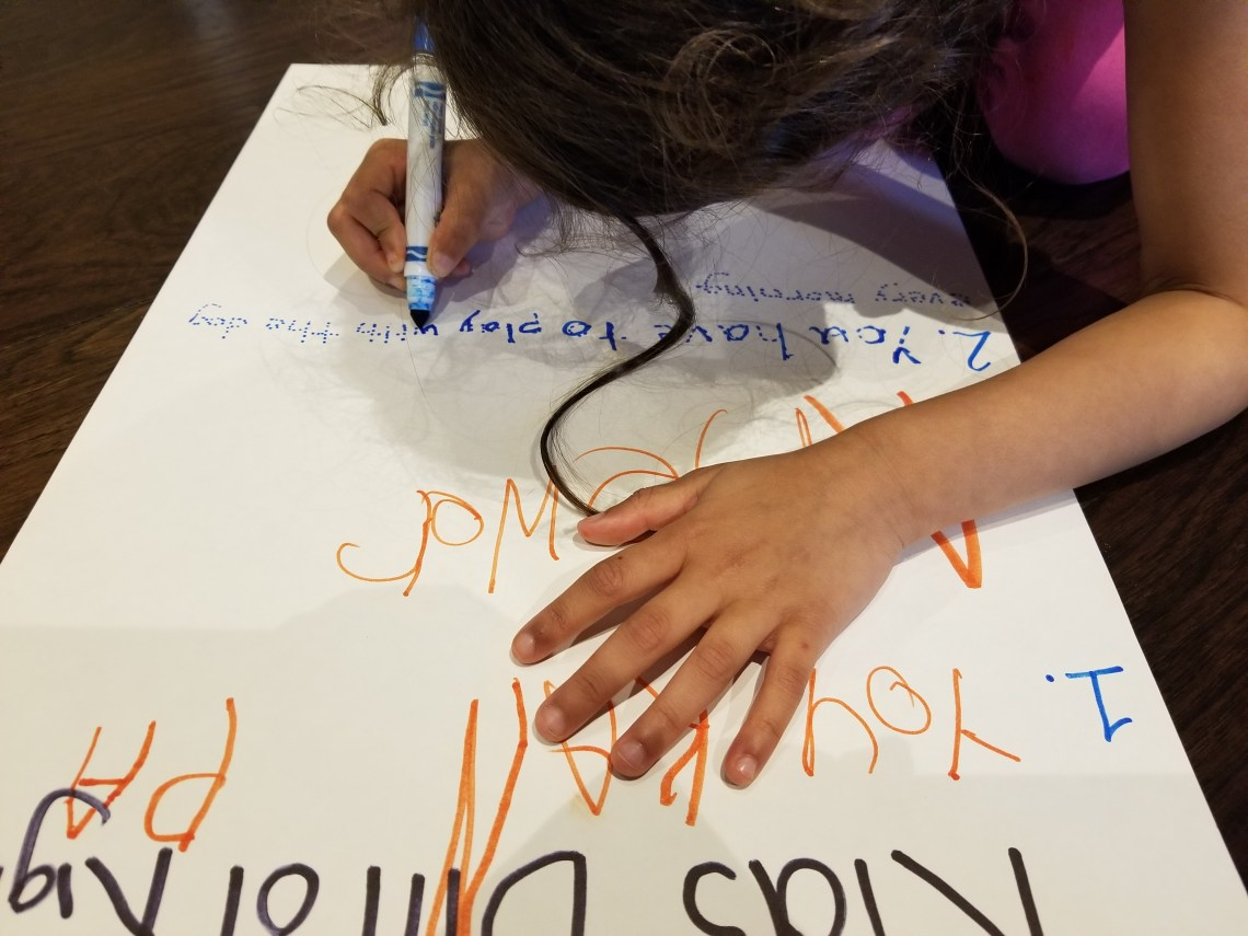 child writing on sheet of paper for Bill of Rights activity