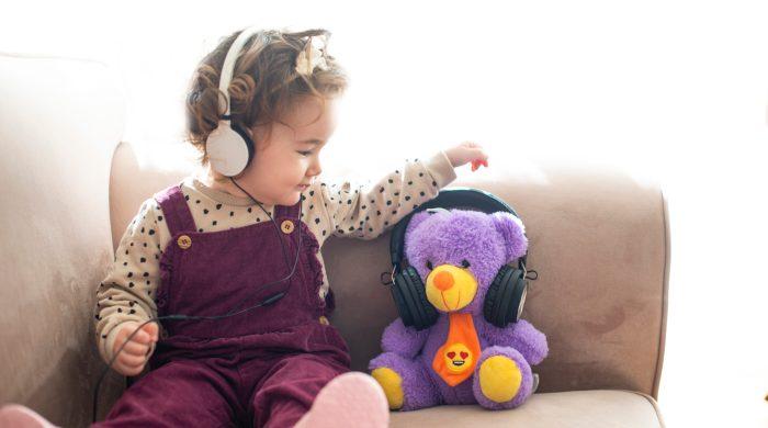 Little girl wearing headphones sitting next to a stuffed bear wearing headphones