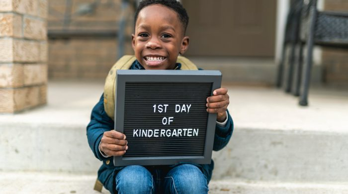 """Little boy holding sign that says """"1st Day of Kindergarten"""""""