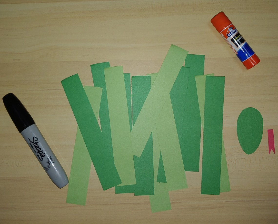 Strips of green construction paper, sharpie, and a glue stick
