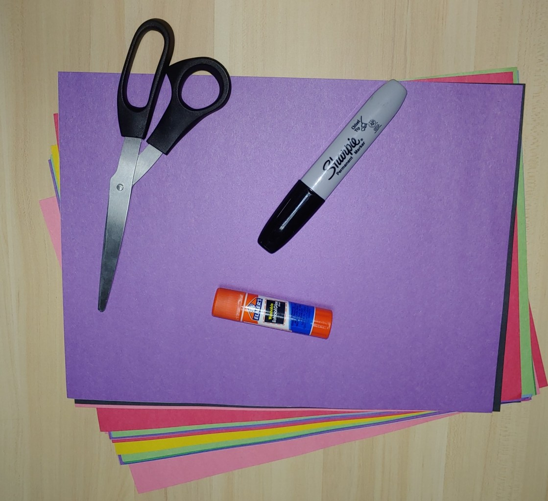Stack of construction paper, scissors, glue stick, and sharpie