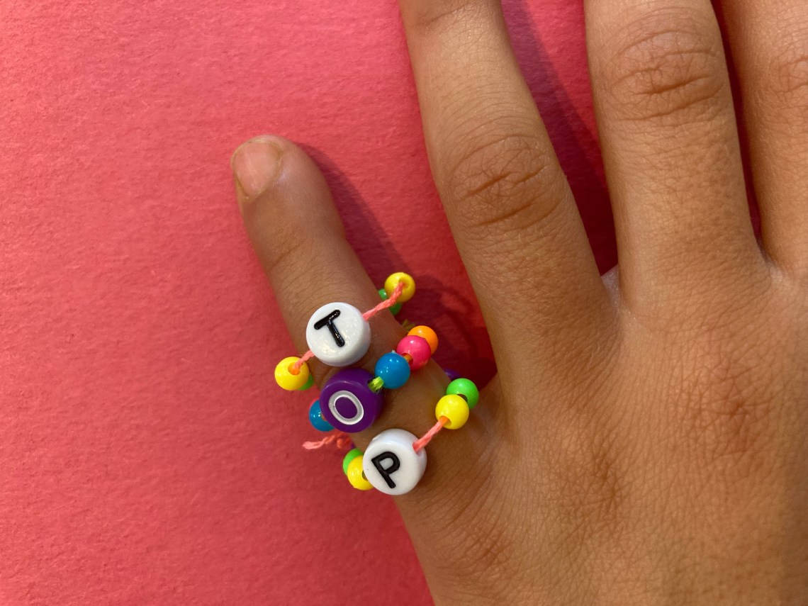 child wearing three bead rings that spells out 'Top'