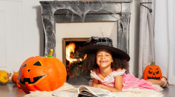 Little girl wearing witch hat reading by a fireplace
