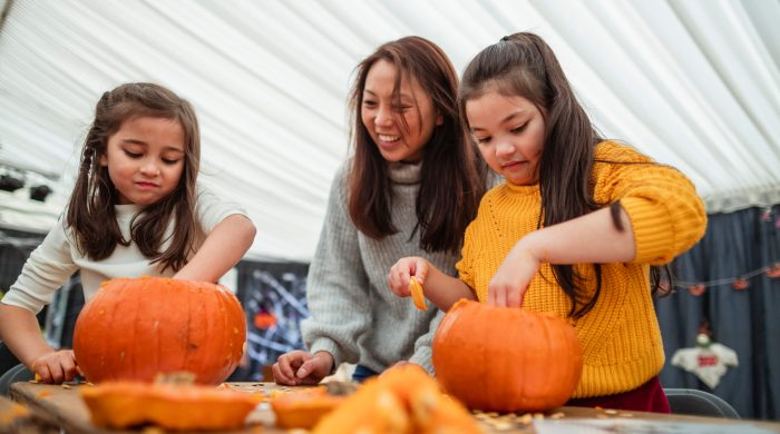 Mother and daughters scooping seeds out of pumpkins