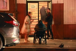 Jaklin sits in her wheelchair, looking away from the camera, and looking into a building with an open glass door, with a flight of stairs inside. It is nighttime, and there are two people who are blurry in the frame that are talking to Jaklin or looking on at her sitting there.