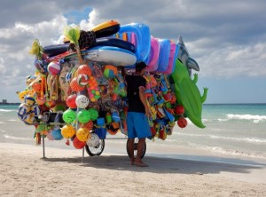 Barrow on beach piled high with inflatable toys and swimming aids