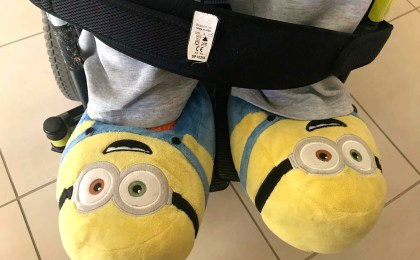 A pair of yellow minion shoes resting on footrest of wheelchair