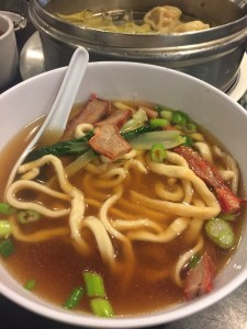 half-eaten bowl of noodles with roast pork soup