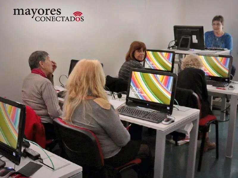 fotografía del grupo de alumnos de los cursos gratuitos presenciales de computación para adultos mayores del Programa de Mayores Conectados, en el aula con la profesora