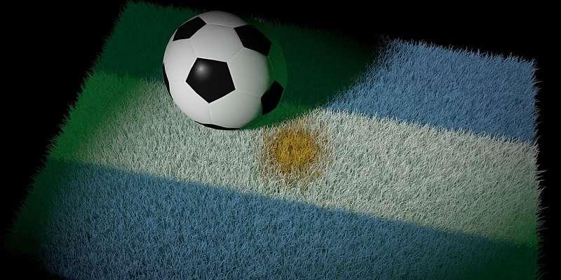 Pelota sobre bandera Argentina, simbolizando que el mundial de fútbol se ve en casa en Argentina