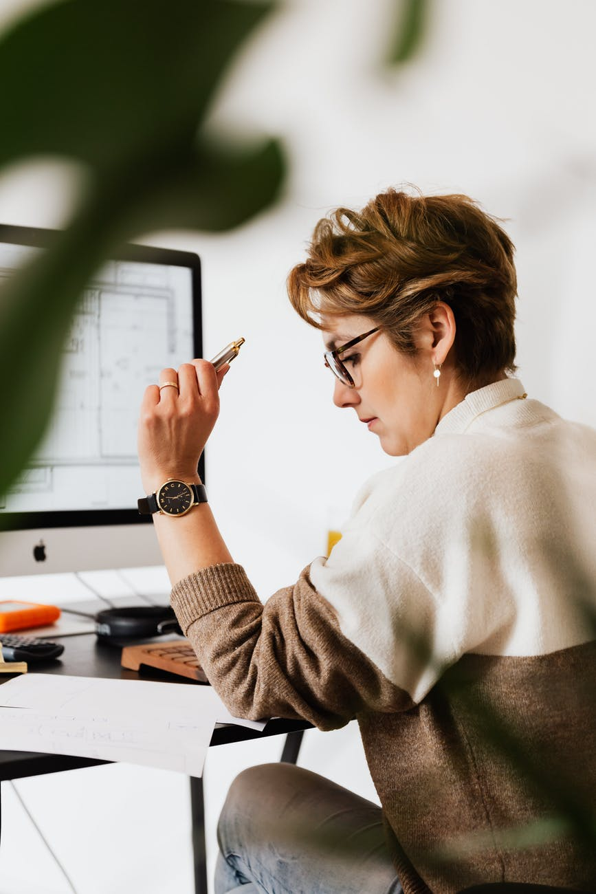 focused businesswoman reading documents and working on computer in office