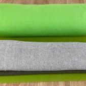 Ausschnitt Grüne Yogamatte auf Holzfußboden mit grünen Yoga-Bolster und zwei übereinander gelegten Decken