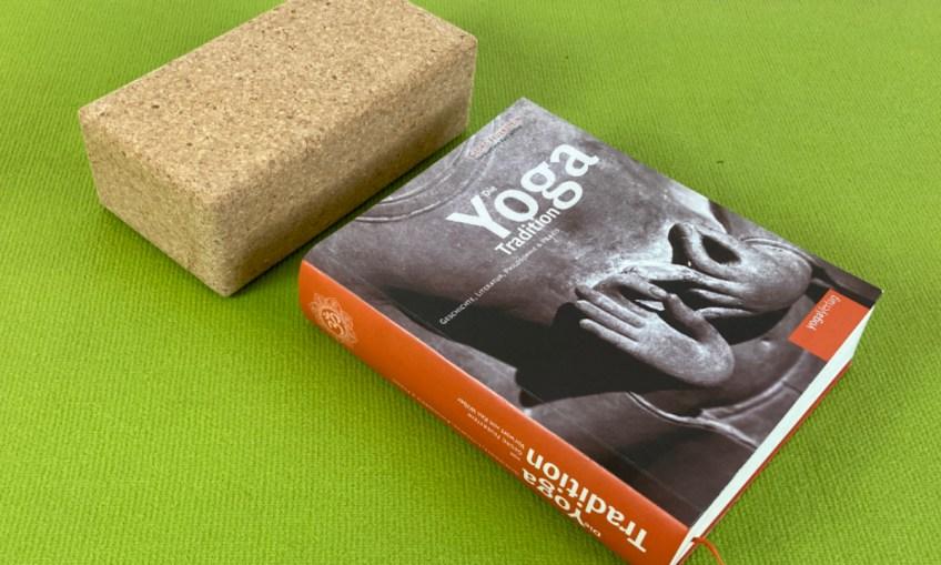 """Ausschnitt Grüne Yogamatte mit einem Yoga-Block aus Kork und einem großen dicken Buch """"Die Yoga Tradition"""""""
