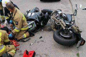 na drodze leżą uszkodzone dwa motocykle, po lewej służby ratunkowe udzielają pomocy rannemu