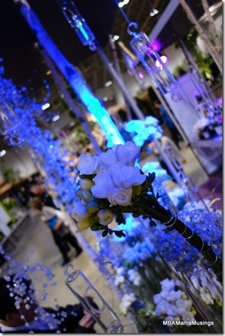 Hanging glass vases and white flowers illuminated by blue light