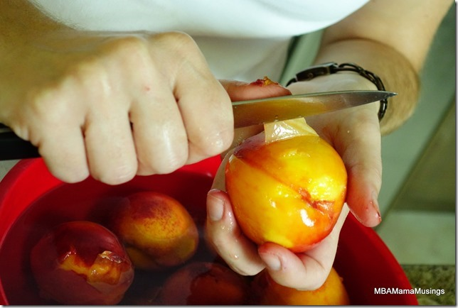 Peeling peaches over a red bowl