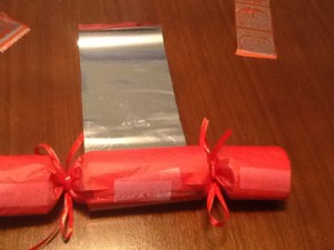 Decorating the red Christmas cracker with stickers