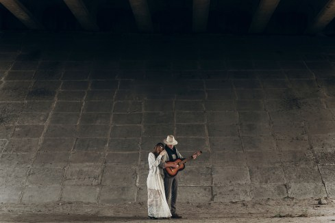 Stylish Hipster Couple Hugging Under Bridge. Man In Hat Playing