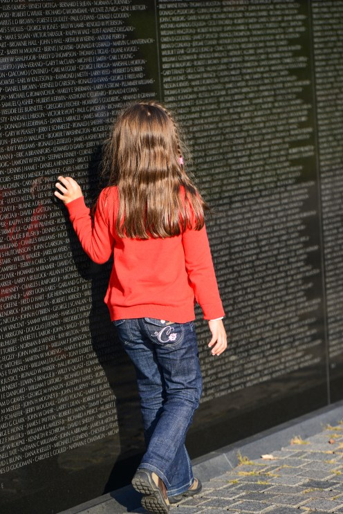 WASHINGTON, D.C. - OCT 29, 2013: Unidentified little girl looks for a name on the wall at Vietnam Veterans Memorial on October 29, 2013, in Washington, D.C.
