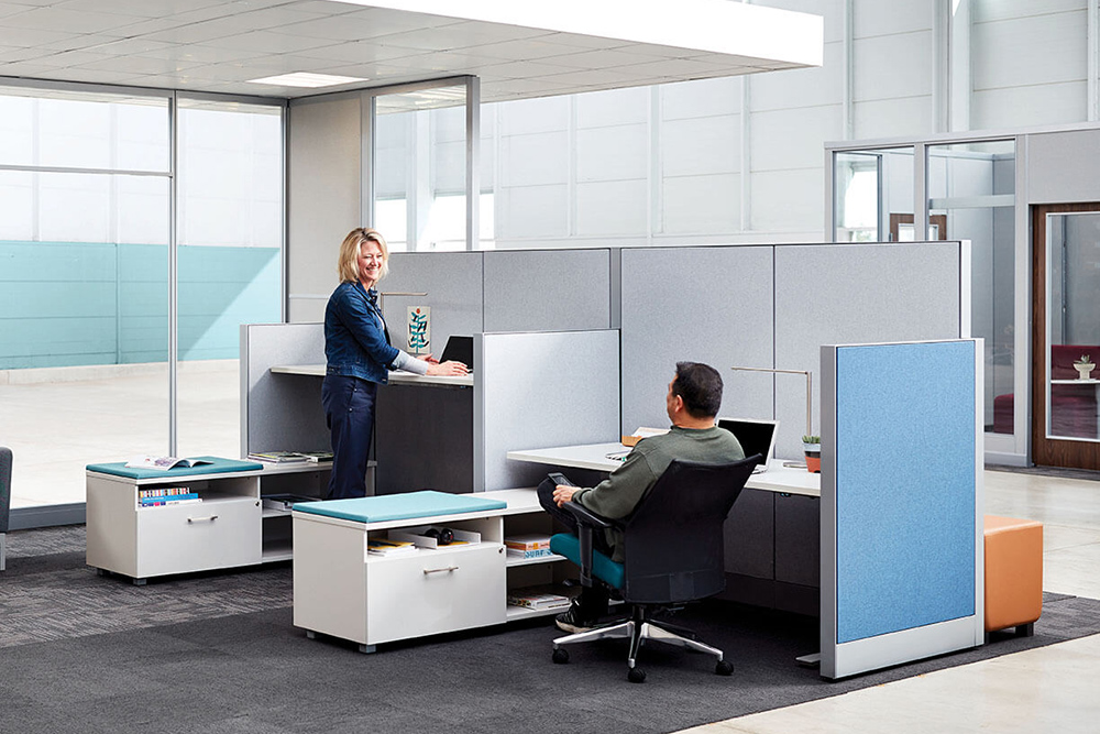 One person standing and one person sitting while they work
