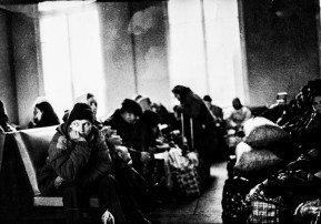 Black and white photograph of crowded train station in post-Soviet Ukraine