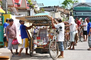 MCC is supplying building materials, including plywood and tin sheets similar to those being loaded onto this bicycle-powered rickshaw, to almost 3,000 families whose homes were destroyed by Typhoon Haiyan. In addition, MCC is paying local people to build the houses in the towns of Naval and Dulag.   MCC Photo by Laura Armstrong.