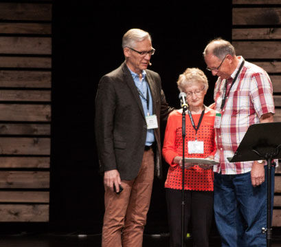 "Willy Reimer paid tribute to  Ralph and Grace Gliege, citing 22 years of  ministry in  Saskatchewan  marked by  perseverance, passion  for Christ and hospitality. ""You are all about relationship,"" said Reimer, presenting the couple  with a serving plate  to symbolize the way  they've graciously hosted others over the years. Photo: Lisa Hamm"