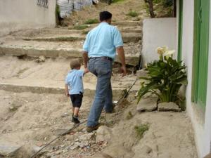 David Bonilla, founder of the Education Brings Hope Children's Centre, walks with Isaac Friesen during his family's visit to the a Global Family project in Cazucá, Colombia. Credit: Cynthia Friesen