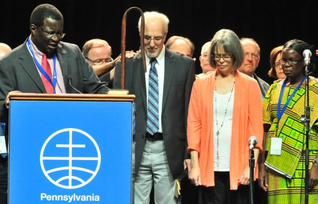 Outgoing MWC president, Danisa Ndlovu, prays after introducing new MWC president, J. Nelson Kraybill, standing with his wife, Ellen Kraybill, and new MWC vice president, Rebecca Osiro. — Dale D. Gehman for Meetinghouse