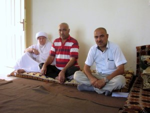 Qasim, right, with his brother Haji, centre, and mother Huda, left, sit in the living area of the new apartment they rent using assistance from a project with MCC's partner organization REACH and funded by a Canadian government grant. Qasim and 28 other relatives were displaced from their homes in Sinjar by an advance of the Islamic State group. They all lived together for 10 months in an unfinished building before receiving rent assistance from REACH and moving to the new apartments. (MCC photo/Kaitlin Heatwole)