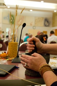 An MCC Canada 2016 annual general meeting delegate grinds wheat kernels with a mortar and pestle during a worship session. MCC photo/Rachel Bergen