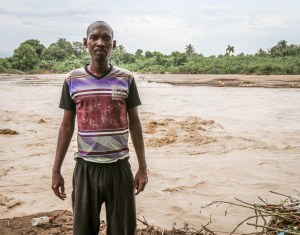 "Hudson Reny-Jean stand beside the River Gris that washed away homes in the Voudray community of Cite Soleil. The flooding also affected the safety of drinking water, making the water purification tablets that MCC provided a blessing, according to Reny-Jean.""He held these 3-cent tablets in his hand and just kept repeating, 'These are such a blessing, these are such a blessing for our community."" (MCC photo/Paul Shetler Fast)"