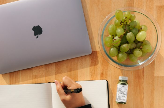 Mac laptop, bowl of  green grapes, bottle of natural supplement, and hand with pen writing in journal