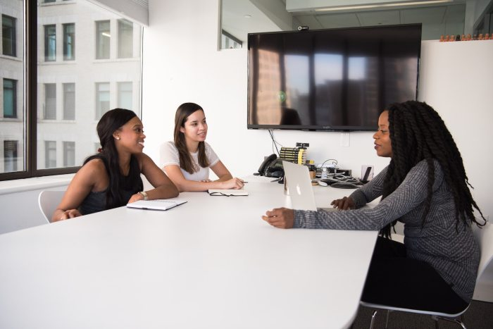 Three women of color meeting in an office, symbolizing the importance of diversity, inclusion and equity in attracting top talent