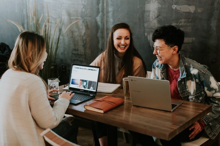 three female employees laughing together with laptops at desk, demonstrating team building