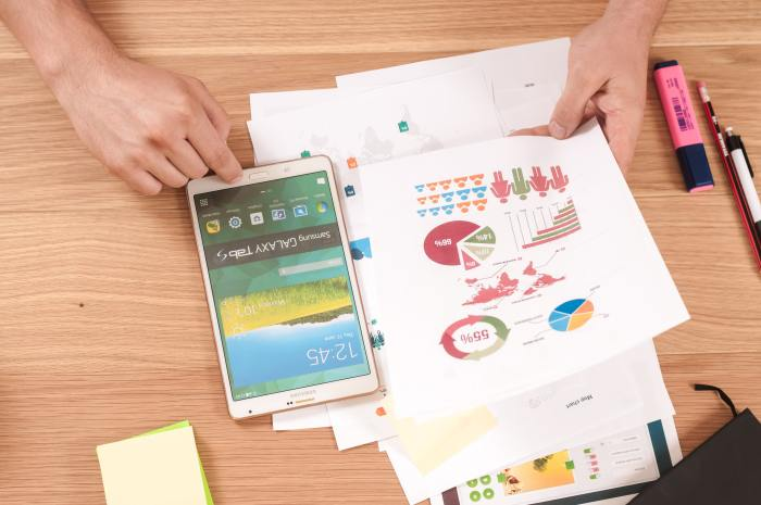 closeup of phone, highlighter, pen, pencil and a stack of documents with charts and graphs, showing someone developing their strategic HR plan