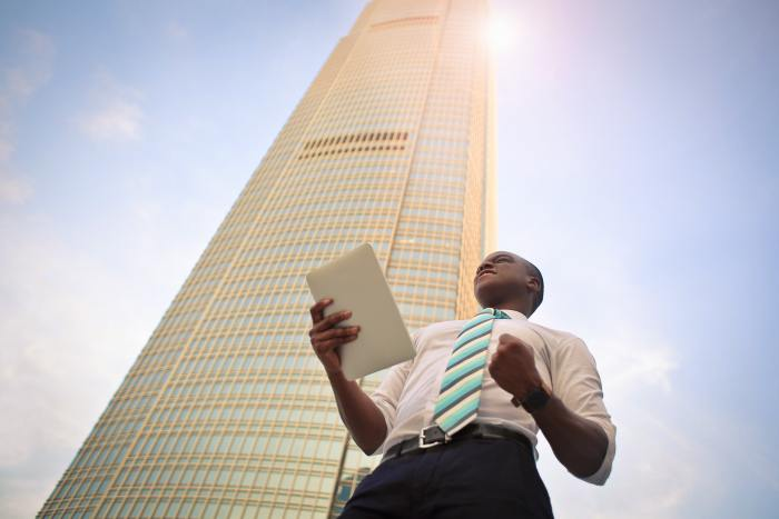 business man holding paper in one hand, with other hand clenched in a fist, celebrating success resulting from strategic HR, with a skyscraper behind him