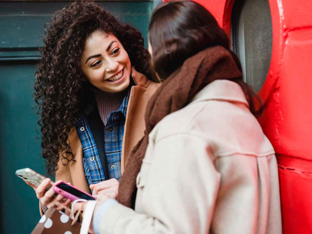 smiling young multiracial ladies browsing smartphones and communicating on street