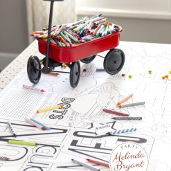 Table set with fun table runner and a red wagon filled with crayons