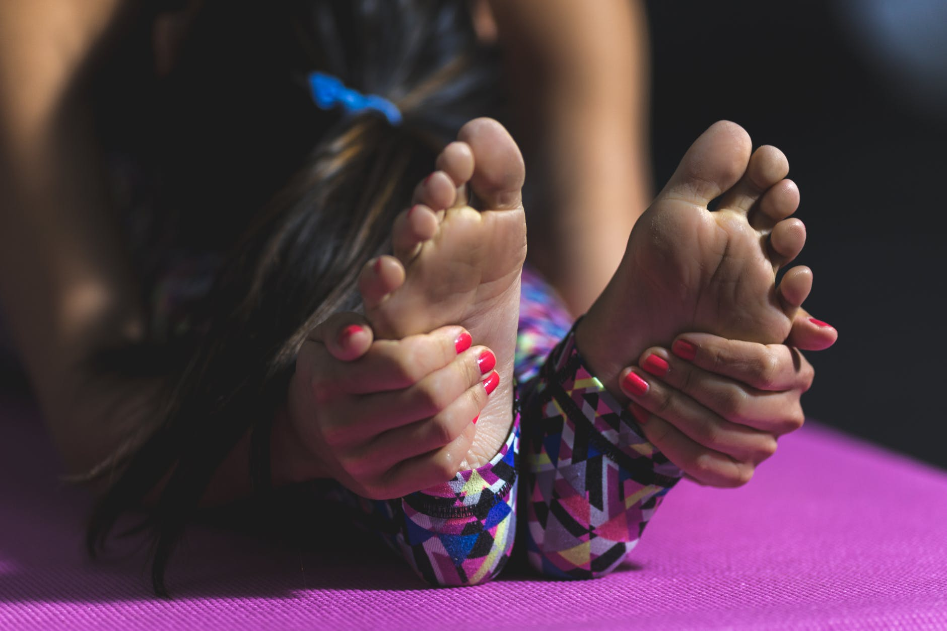 hands grasping feet during a yoga stretch