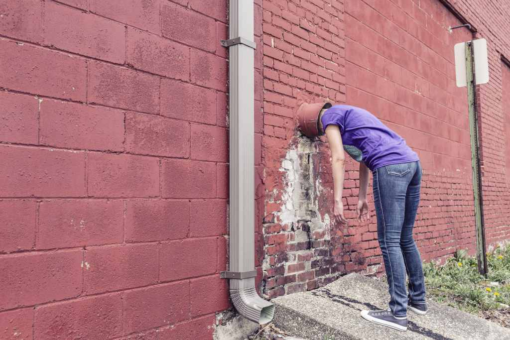 a man with his head stuck in a wall