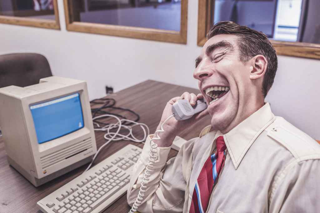 Man at desk, laughing into the phone