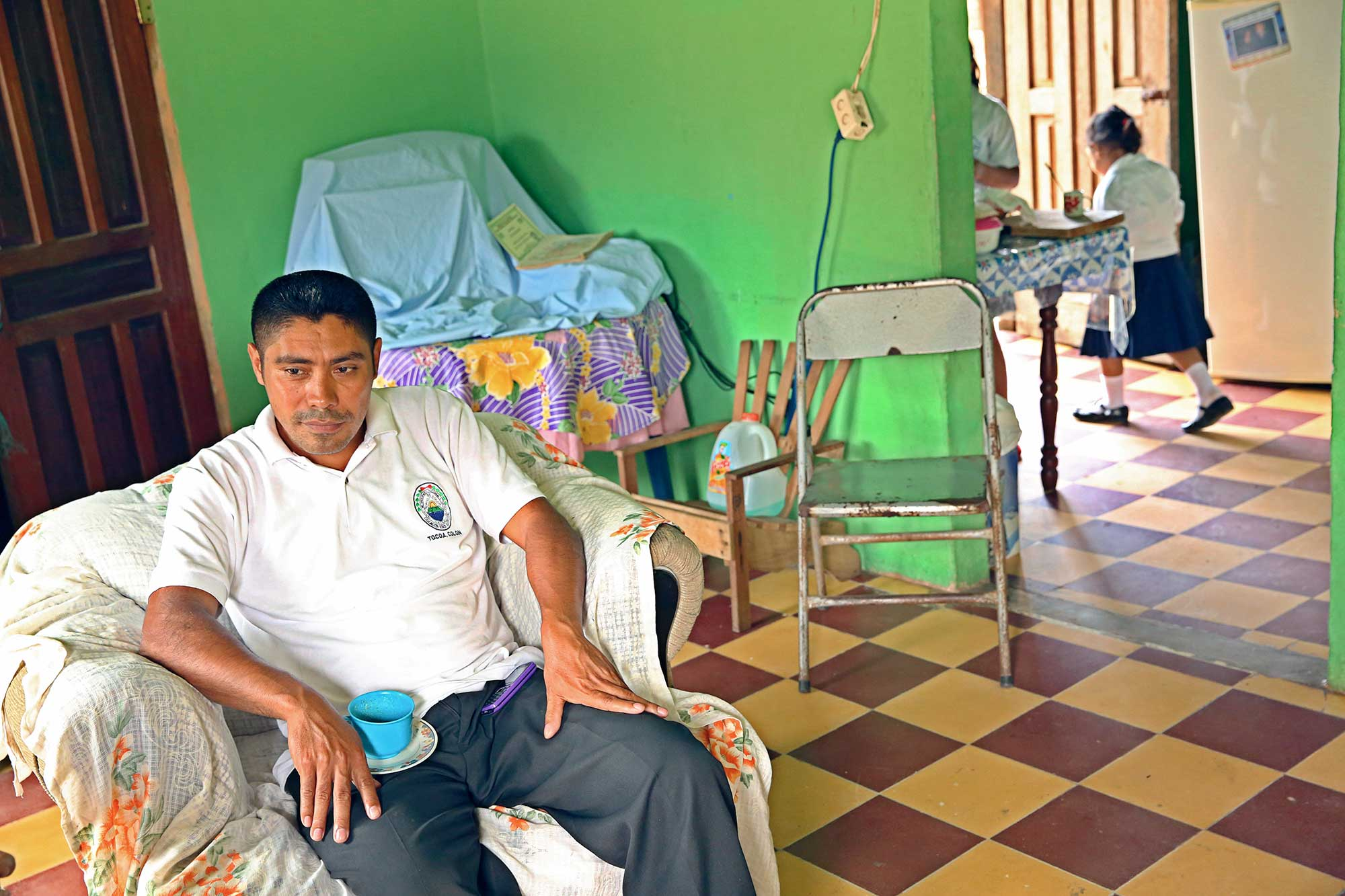 Nicolas Rosales sits in his living room, one of his daughters walks through in the background.
