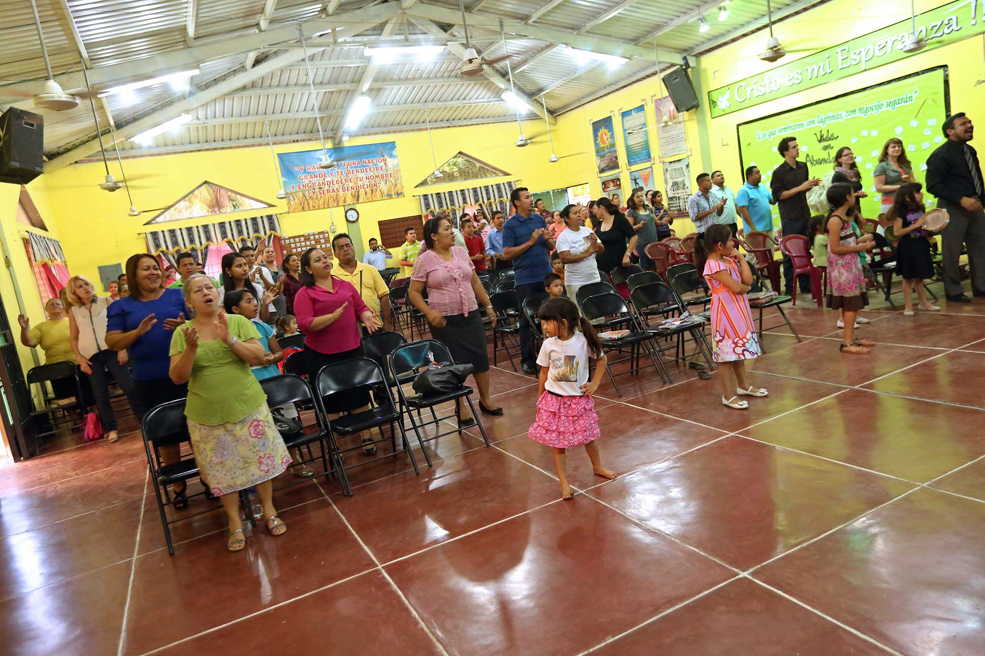 A congregation participate in worship with children at the front