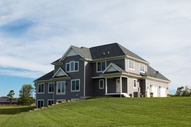 Two story home with grey siding and white trim