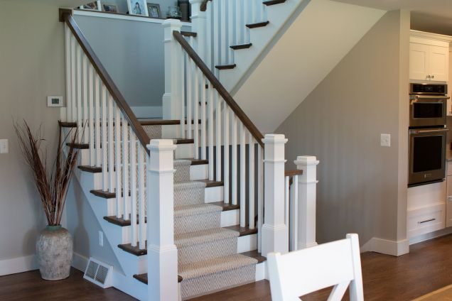 Wood stairway with carpet runner and painted ballusters