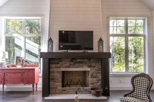 Stone fireplace with timber surround and wood planks on walls